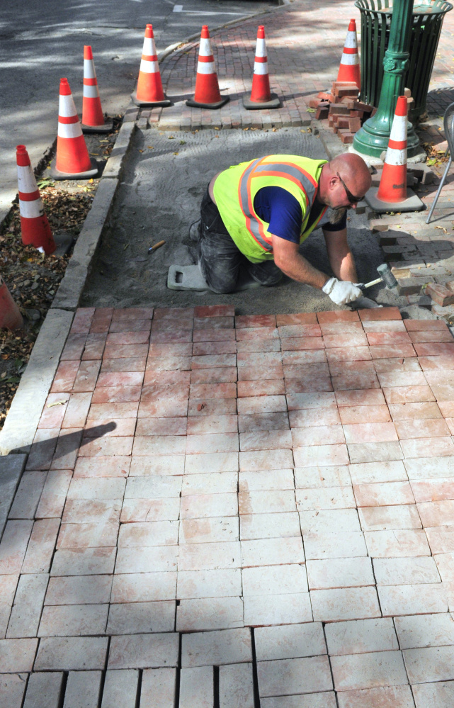 City worker Dan Robideau rebuilds the brick sidewalk in front Gardiner Co-op on Tuesday on Water Street in Gardiner.