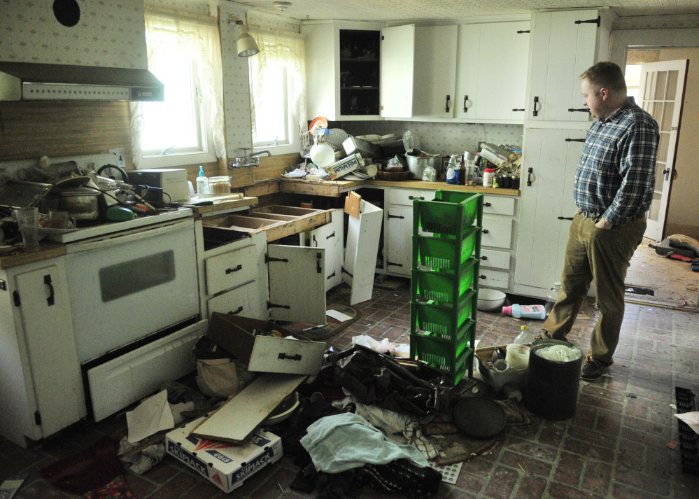 Richard Fortin, librarian at Charles M. Bailey Public Library, looks at the kitchen of 36 Bowdoin St. on Tuesday in Winthrop. The building is one of two homes that are expected to be demolished to make way for a parking lot.