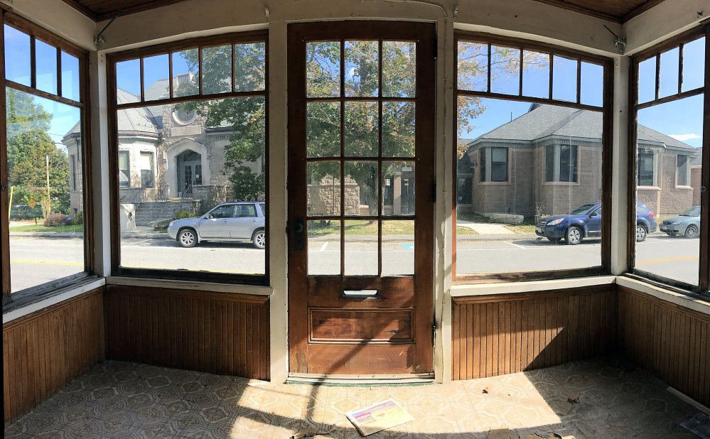 Charles M. Bailey Public Library is seen framed through front porch of 40 Bowdoin St. on Tuesday in Winthrop. The Town Council voted Monday to allow the library to tear down the building to make room for a parking lot.