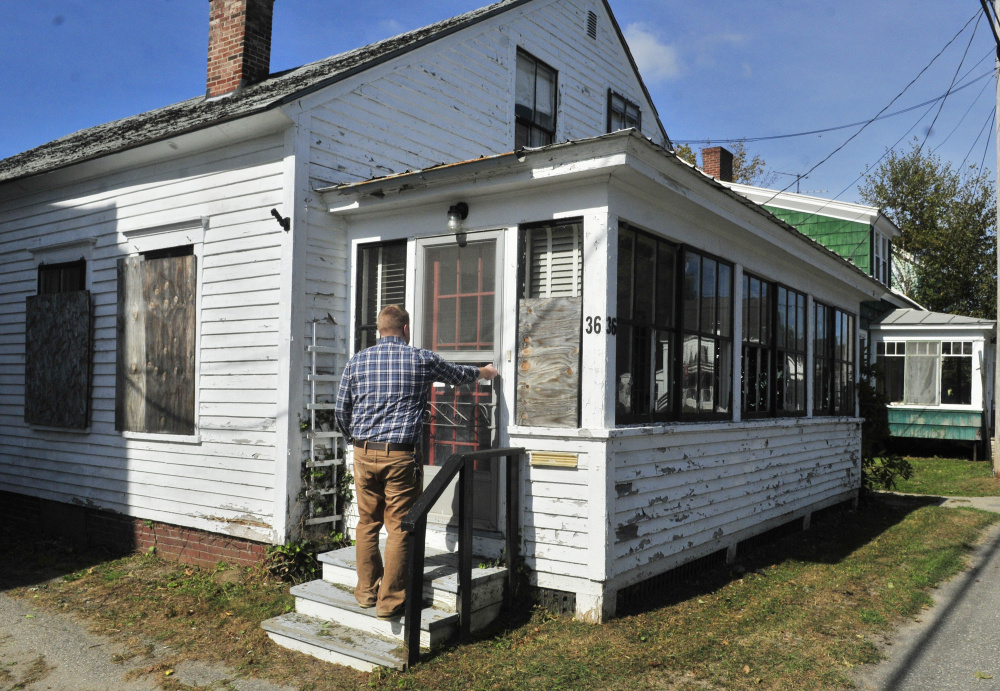 Richard Fortin, librarian at Charles M. Bailey Public Library, unlocks 36 Bowdoin St. on Tuesday in Winthrop, one of two buildings across the street from the library are expected to be demolished to make way for a parking lot.