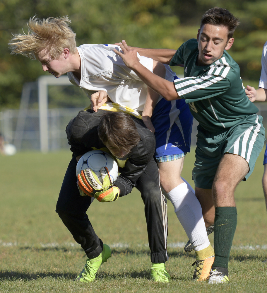 Oak Hill High School's Max Hall, center, and keeper Cole Whitten collide with Winthrop's Jared McLaughlin during a Mountain Valley Conference game Wednesday afternoon in Wales.