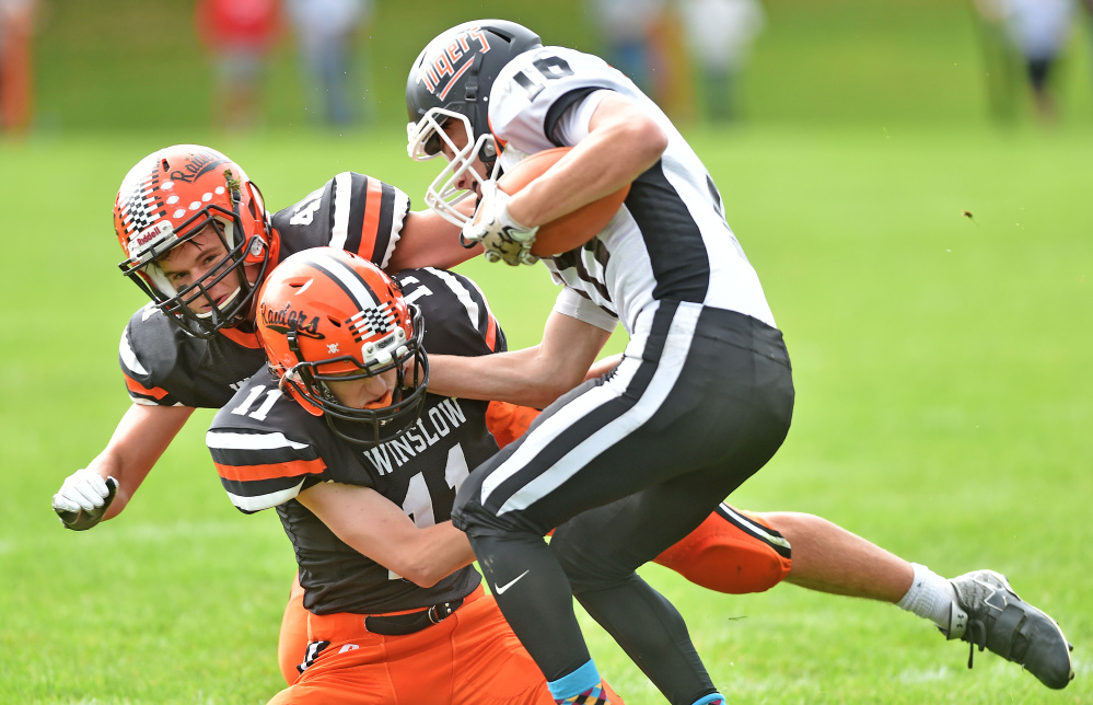 Gardiner's Collin Foye (16) gets tackled by Winslow's Tom Tibbetts (11) center, and teammate Benjamin Dorval (41) back left, Saturday in Winslow.