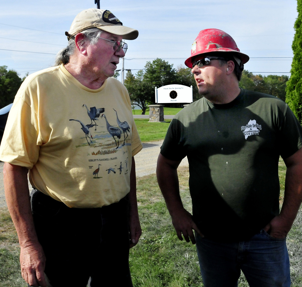 Phil Frizzell, left, of the Palermo Community Center, speaks with driller Chad Grignon, of Pine State Drilling, who was finishing drilling a new well for the center.