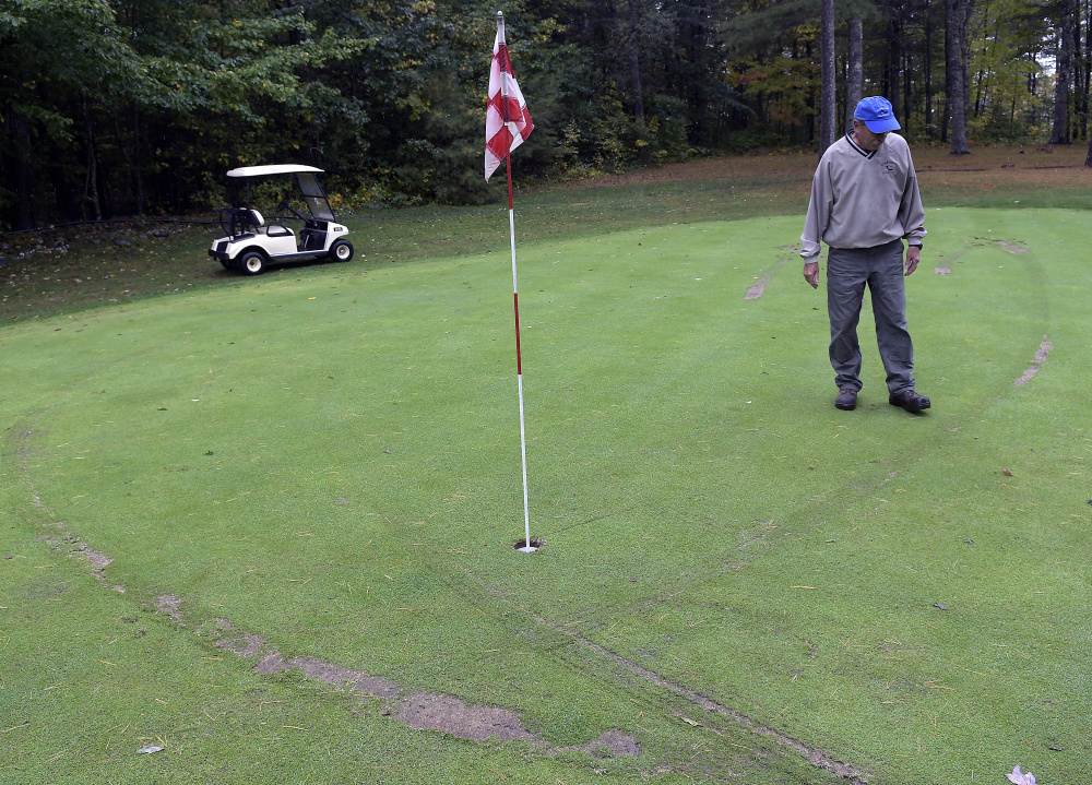 Ruts from golf carts surround Bill Sylvester on the second green at Cobbossee Colony Golf Course in Monmouth on Monday. The Sylvester family discovered Monday that several parts of their course were vandalized by golf carts overnight.