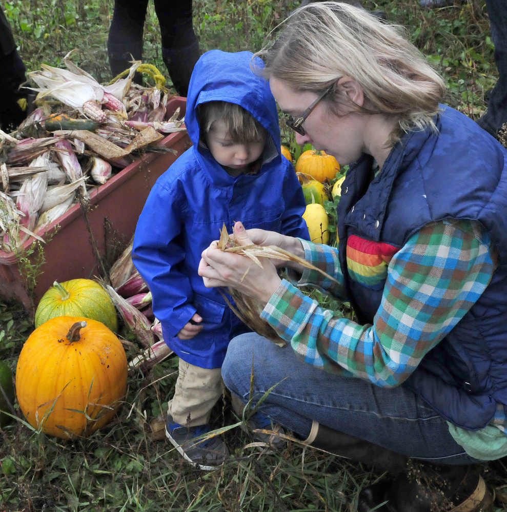 Cate Jacques shows her son Theodore corn produced using the Three Sisters planting technique of planting corn, squash and beans in a single mound during an Indigenous Peoples Day celebration at the Sweet Land farm in Starks on Monday.