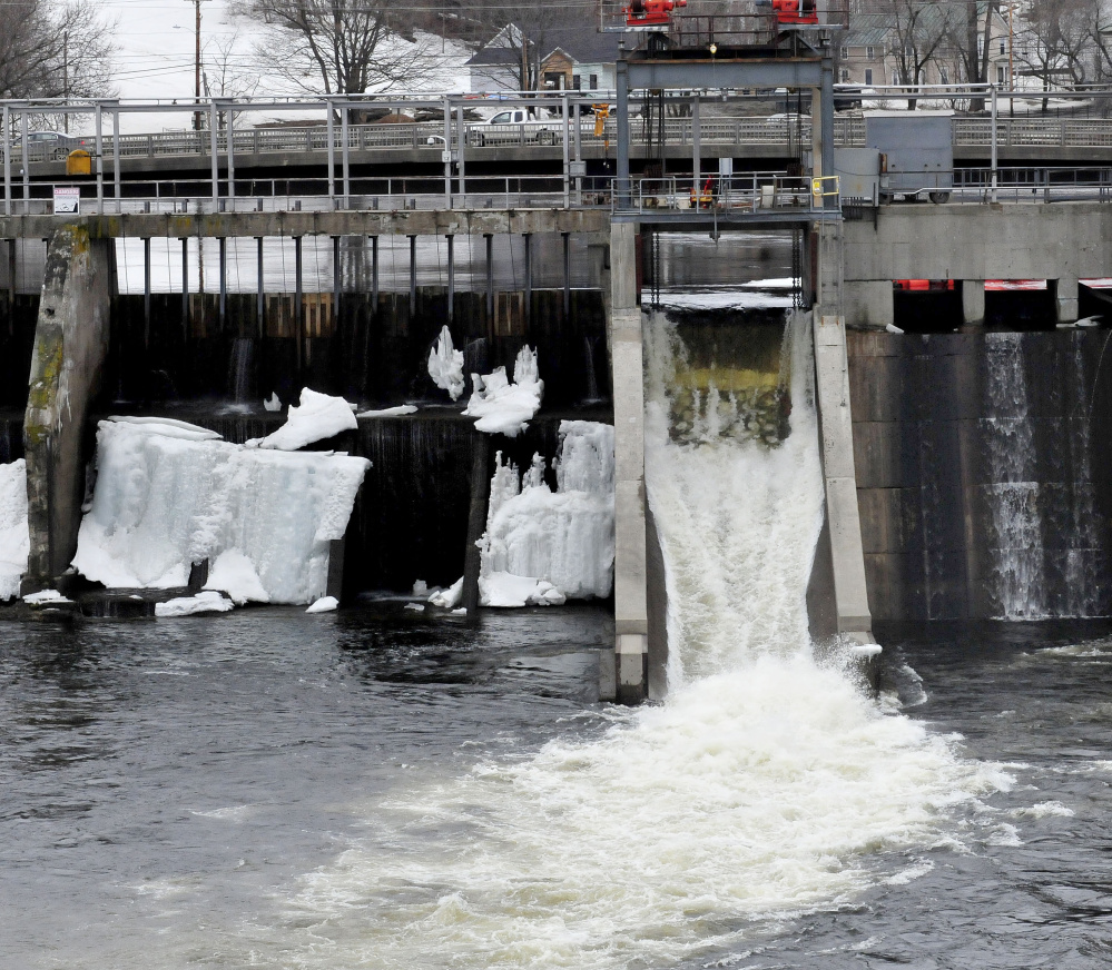 Water flows out of the Weston dam in Skowhegan during ice out in April 2017. Concrete repairs forced a drawdown of 9 feet of the Kennebec River on Oct. 4 to allow repair crews to reach affected areas.