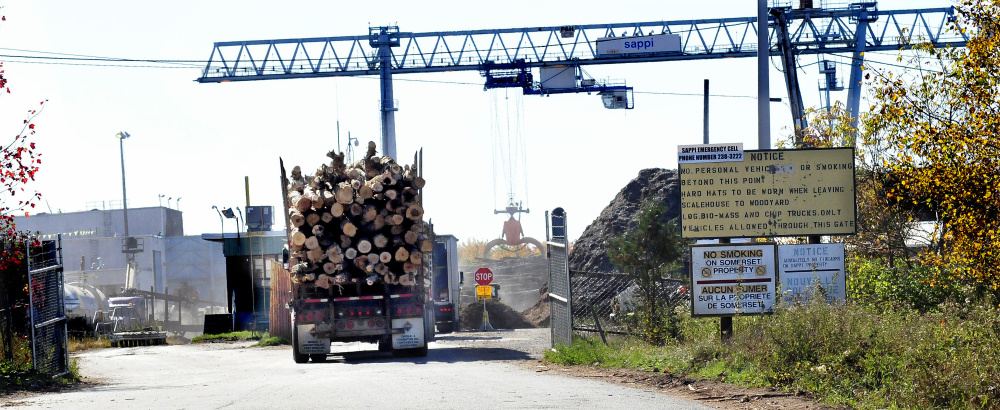 Pulp trucks loaded with wood enter an entrance to SAPPI mill in Skowhegan a short time after a fire was reported at the mill on Thursday.
