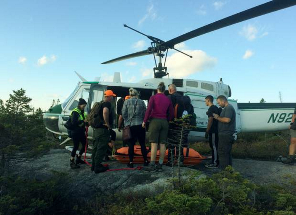 Rescuers carry Kelsey Lampher, of Phoenix, Ariz., to a helicopter after she injured her ankle Tuesday while hiking the Appalachian Trail on Bemis Mountain in Township D in northern Franklin County.