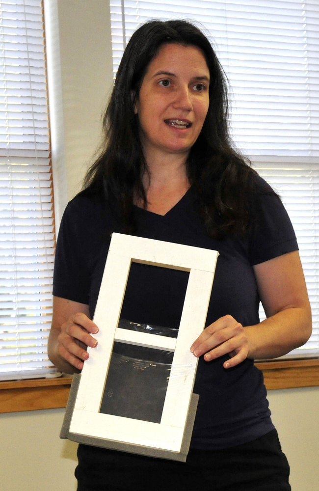 Laura Seaton, a representative of the WindowDressers program, shows a window insert on Wednesday that can reduce energy consumption to members of the Vassalboro FAVOR committee.