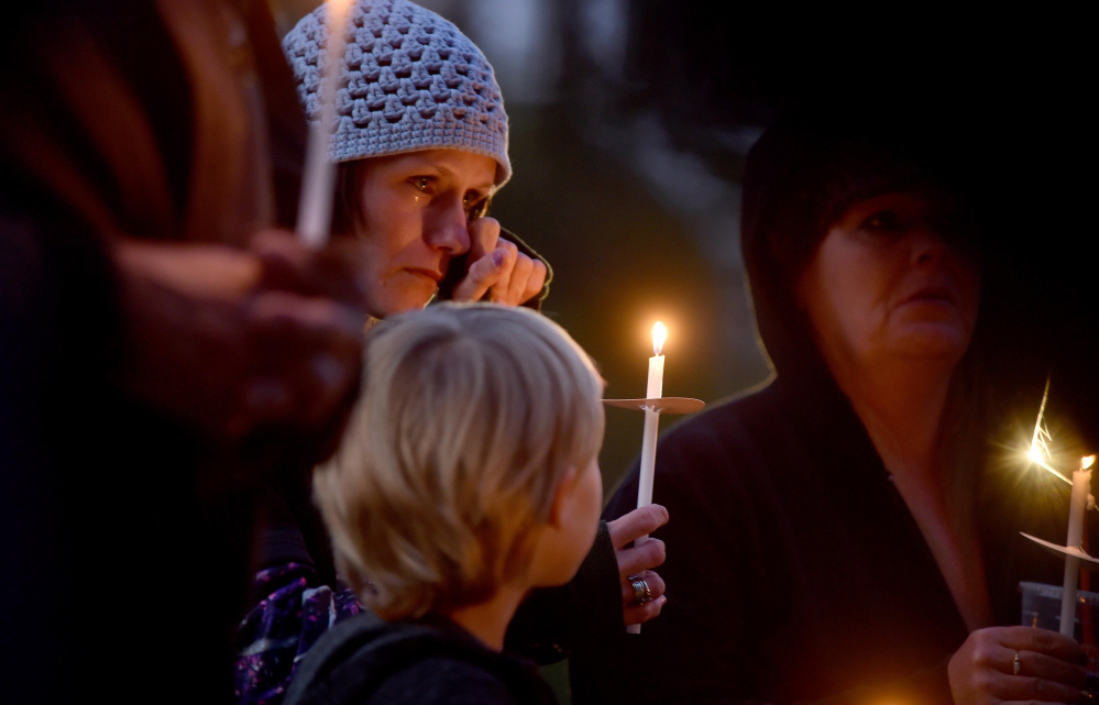 Jessica Hainer, who described herself as a victim of domestic violence, becomes emotional Thursday as she stands with her daughter Shayla, 8, during a domestic violence awareness candlelight vigil at the gazebo at Coburn Park on Water Street in Skowhegan.