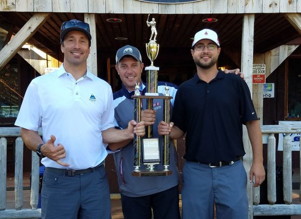 Seth Wescott, left, presents a trophy to members of the winning team from Darlings, Adam Orser and Ashley Fifield.