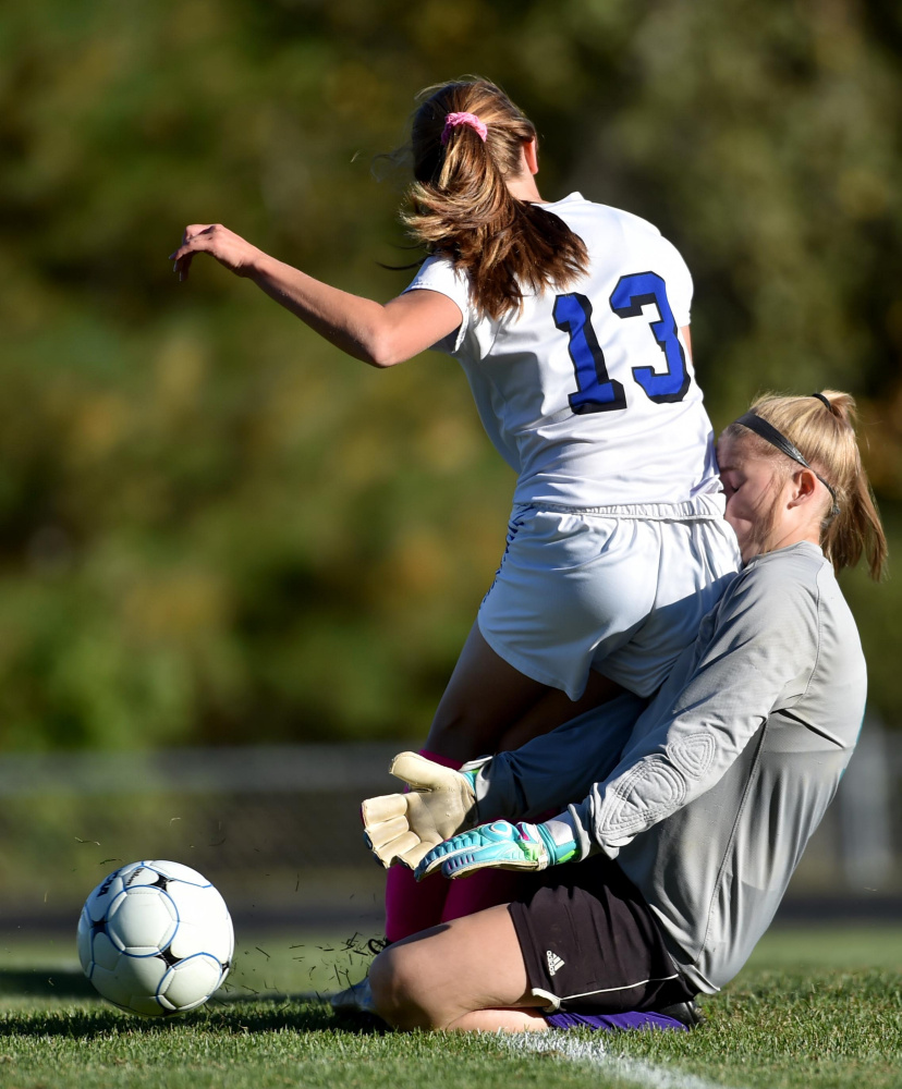 Erskine sophomore Morgan Presby (13) collides with Waterville goalie Aly Drew during a Class B North game Friday in South China.