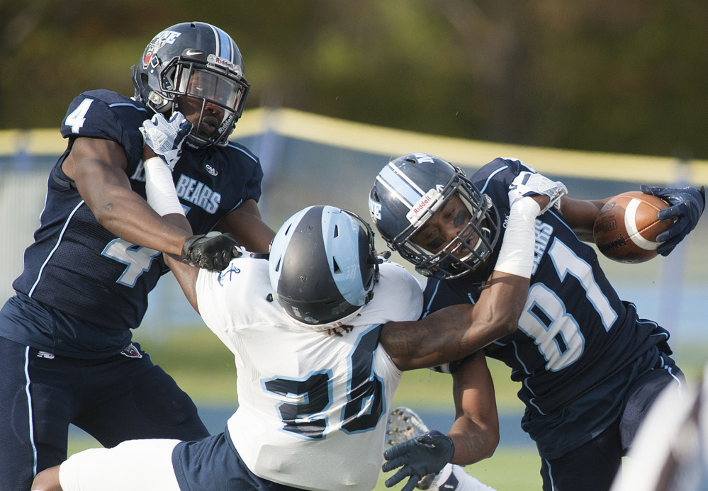 University of Maine receiver Earnest Edwards, right, and teammate Jared Osumah get hooked by Rhode Island defender Manny Patterson during the first quarter Saturday at Orono.
