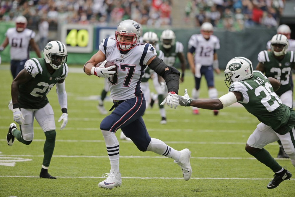 New England Patriots tight end Rob Gronkowski (87) runs away from New York Jets defensive back Marcus Maye (26) and Morris Claiborne for a touchdown during the second half Sunday.