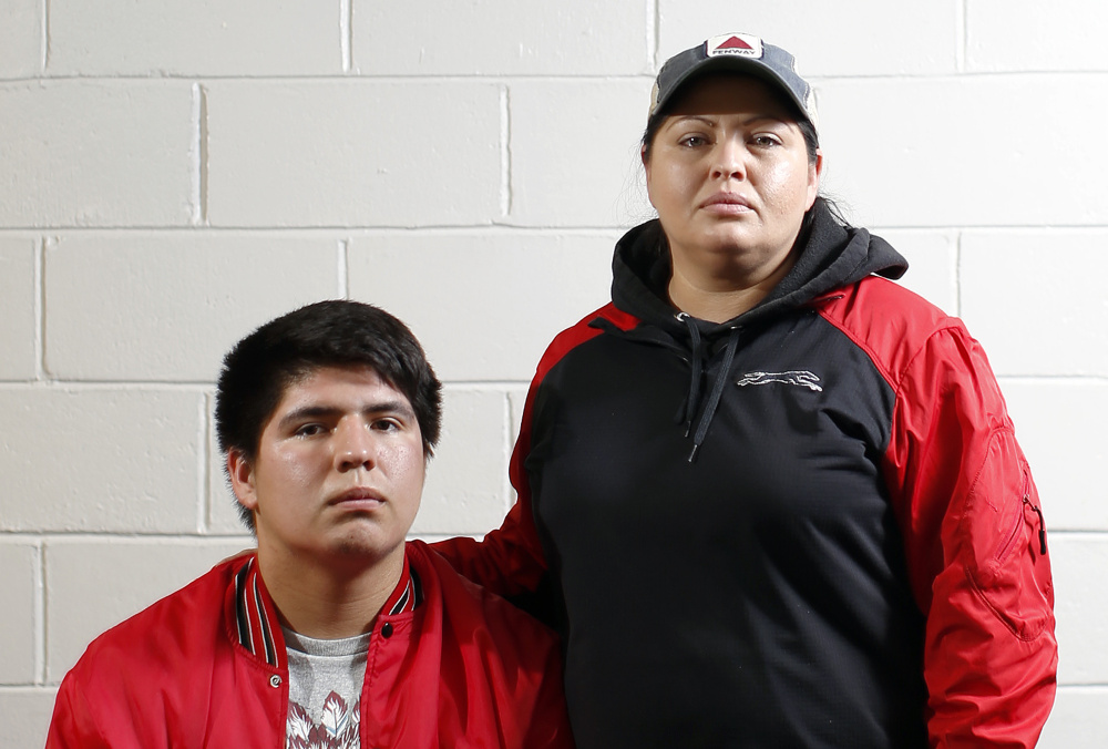 Lucas Francis, left, quarterback of Lisbon High School, and mother Amelia Tuplin are Micmac Indians. Tuplin says she is appalled at racially-charged behavior exhibited by Wells fans during a Class D South game last Friday night in Wells.