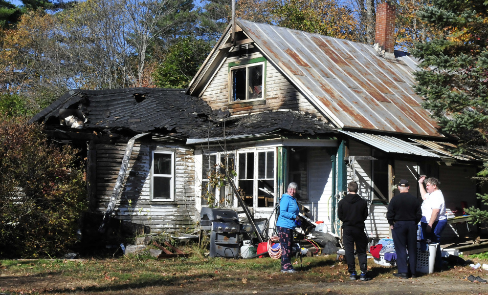 Homeowner Frank Donahue, right, speaks with family members Wednesday outside his home on North Main Street in Strong after fire heavily damaged the home earlier in the morning. Donahue was salvaging items and waiting for an insurance adjuster.