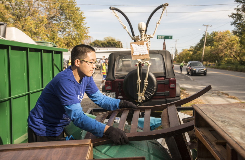 Colby College senior Zhuofan Zhang unloads a chair from a trailer to be disposed of Saturday during an areawide cleanup coordinated by Colby College and the South End Neighborhood Association's Quality of Life Committee on Water Street in Waterville's South End neighborhood.