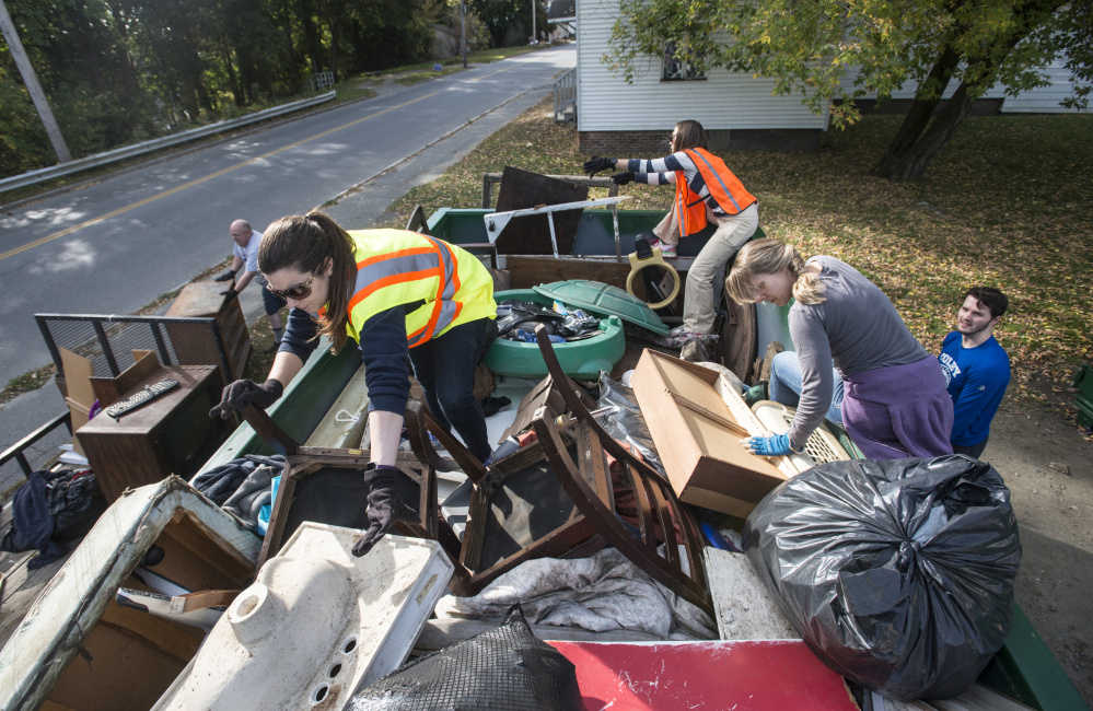 Colby College staff members Laura Jones-Pettit, left, Katie Sawyer, right, and Megan Marsh, back, organize a dumpster of trash collected Saturday during an areawide cleanup coordinated by the college and the South End Neighborhood Association's Quality of Life Committee on Water Street in Waterville's South End neighborhood.