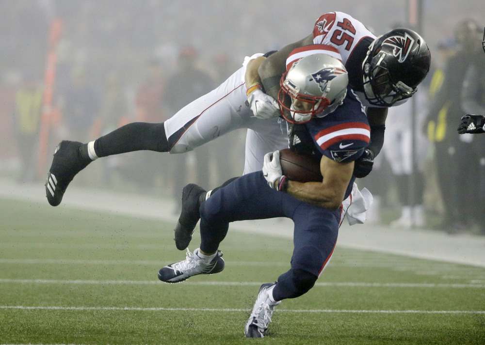 Atlanta Falcons linebacker Deion Jones tackles New England Patriots wide receiver Chris Hogan during the second half Sunday in Foxborough, Massachusetts.
