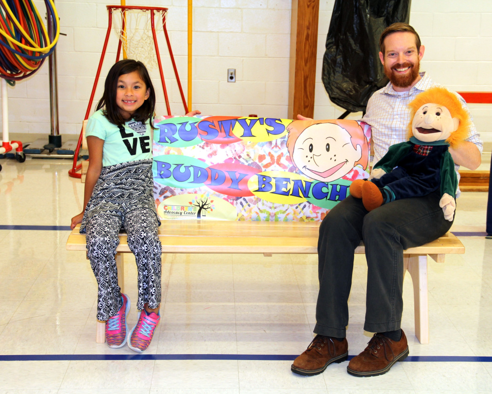 Atwood Primary student and Create a Hero contest winner, Prudence Baltazar, left, and Sexual Assault Crisis and Support Center Educator Sean Landry on Rusty's Buddy Bench at Atwood Primary School in Oakland.