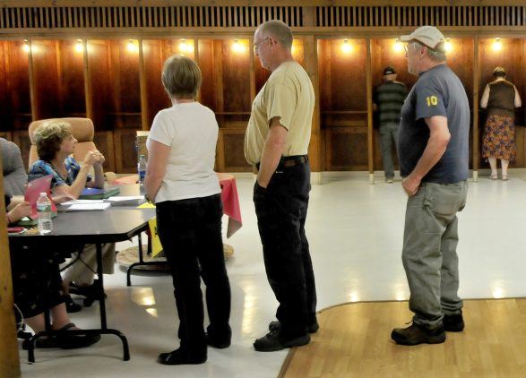 Residents in the 10 towns that make up the RSU 9 district will vote for the fourth time on a school budget on Tuesday. Farmington residents wait in line to obtain ballots for the school budget vote at the Community Center in Farmington on Sept. 11.