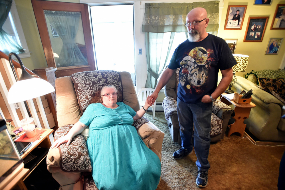 Mona and Howard Gagnon hold hands July 7 in their living room in Waterville.