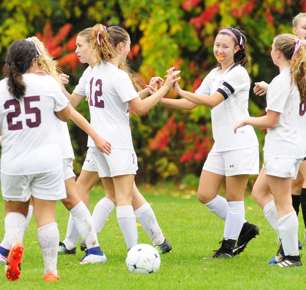 Teammates congratulate Monmouth's Tia Day, second from right, after she scored her fourth goal against Maranacook in a Class C South quarterfinal game Tuesday at Monmouth Academy.