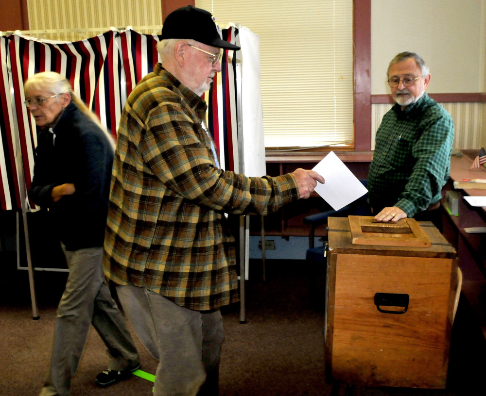 "New Sharon resident Bob Neal casts his ballot Tuesday in the Regional School Unit 9 school budget referendum as warden Forrest Bonney watches. Mercy Hanson had just cast her ballot. Bonney said turnout was light in early afternoon. ""I call it voter fatigue,"" Bonney said referring to the fourth vote on the budget."