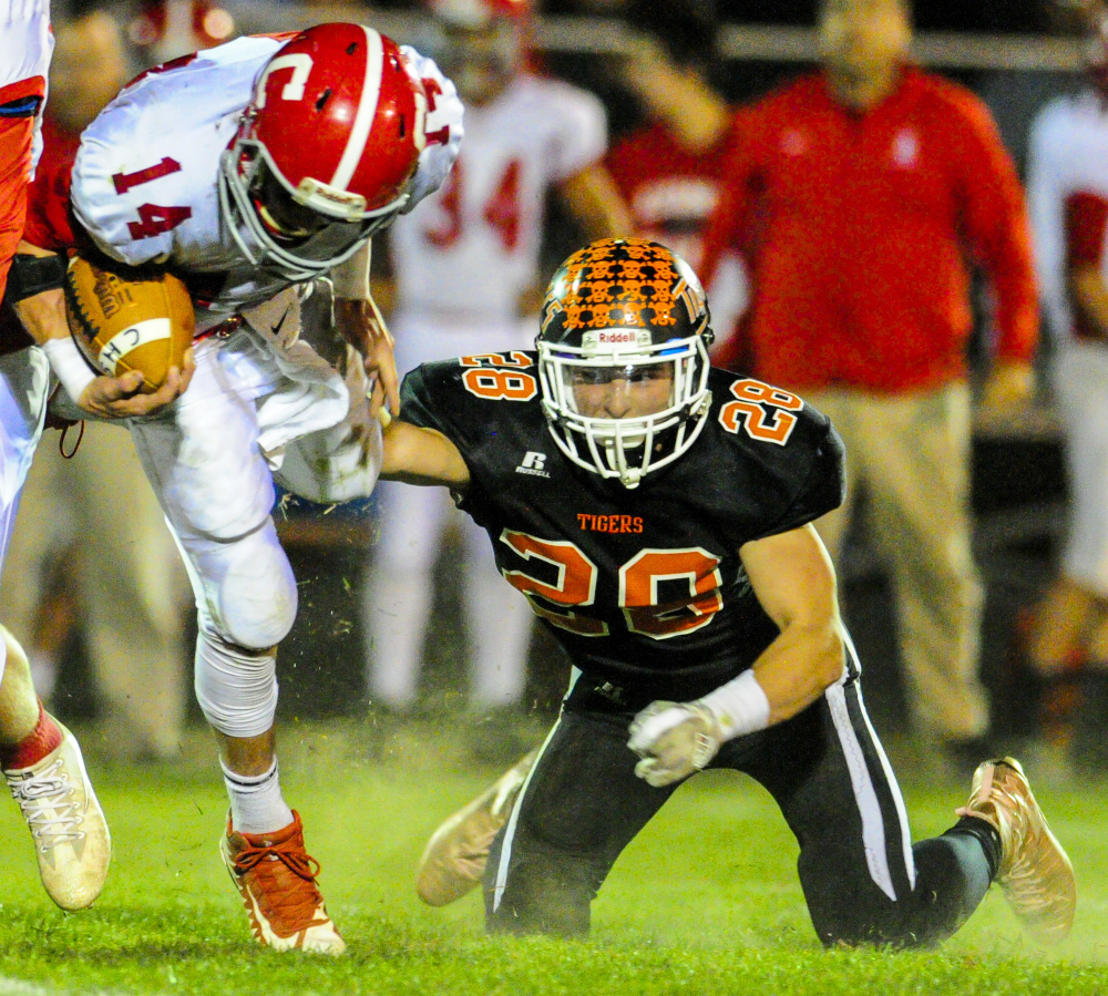 Cony quarterback Anthony Sousa gets tripped up by Gardiner's Garrett Maheux last week at Hoch Field in Gardiner.