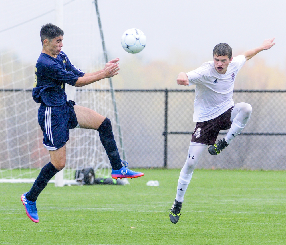 Traip's Pablo Lopez Zapata, left, and Monmouth's Thomas Neal go up for a ball during a rain soaked Class C South quarterfinal game Thursday at Kents Hill School.