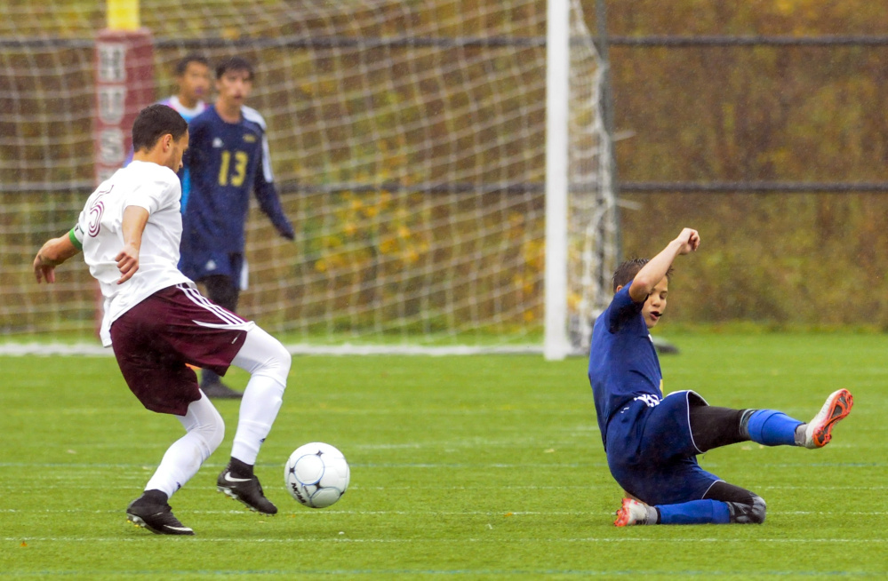 Monmouth's Nick Dovinsky moves the ball upfield as Traip's Frankie Driscoll misses a slide tackle during a rain soaked Class C South quarterfinal game Thursday at Kents Hill School.