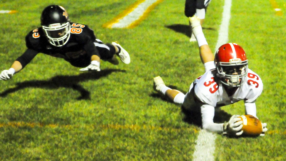 Cony's Elijah Dutil, right, catches a pass just short of the goal line as Gardiner's Matt Boynton plays defense during a game Friday at Hoch Field in Gardiner.