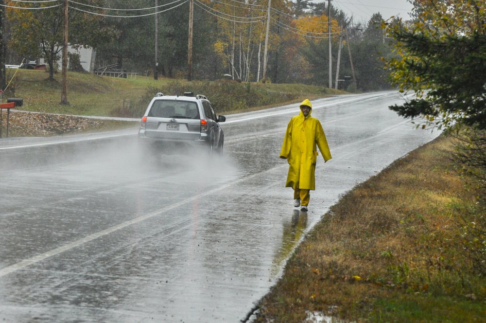 Andrew Nichols wears yellow rain gear as he walks Wednesday along Civic Center Drive in Augusta. Nichols finished his shift at Home Depot and was walking in the pouring rain to get to his home on Summerhaven Road. More rain is expected from Sunday night into Monday.