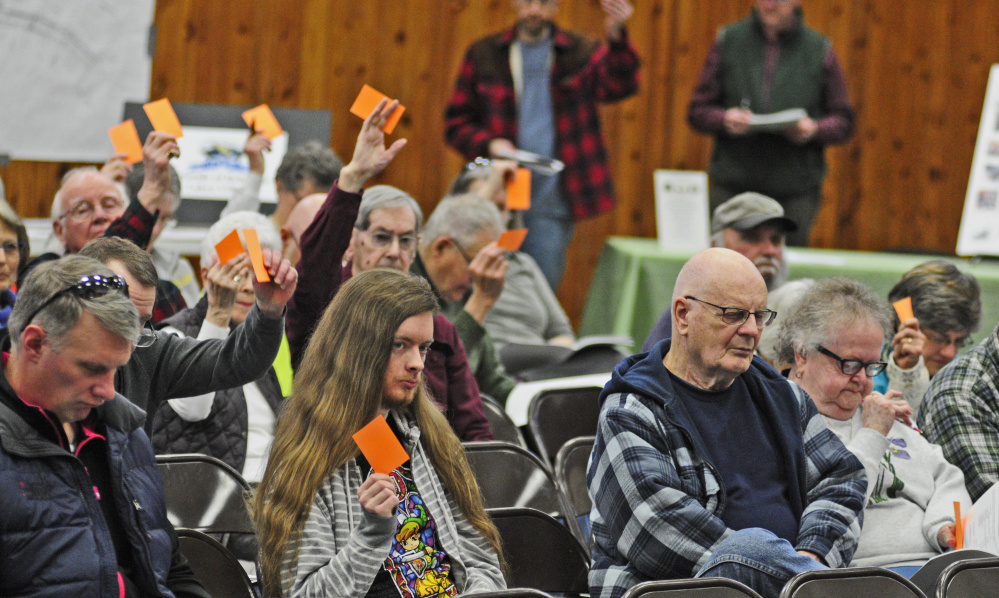 Residents hold up cards March 18 to vote during the Belgrade Town Meeting at the Center For All Seasons, where another meeting will be held Monday to discuss the town's possible withdrawal from Regional School Unit 18.