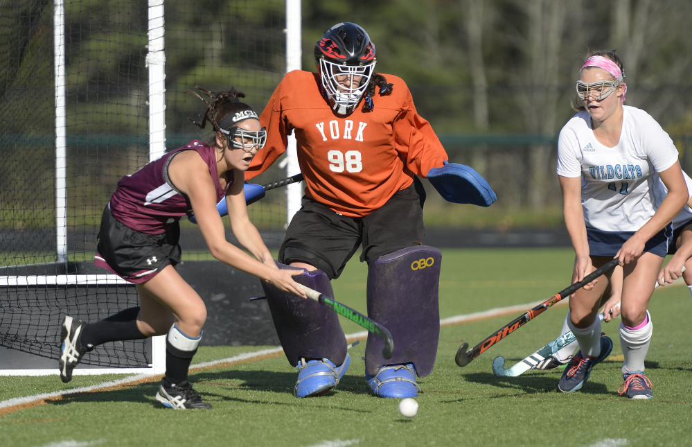 York goalie Julianna Kiklis and Caroline Leal defend the goal as MCI's Madisyn Hartley tries to get off a shot during the Class B state championship game Saturday at Falmouth High School.