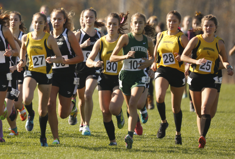 Maranacook team members, including Molly McGrail (27), Dana Reynolds (30), Sophie O'Clair (28) and Madelyn Dwyer (25) run with the pack during the start of the Class C cross country state championship meet Saturday at Twin Brooks Recreation Area in Cumberland.