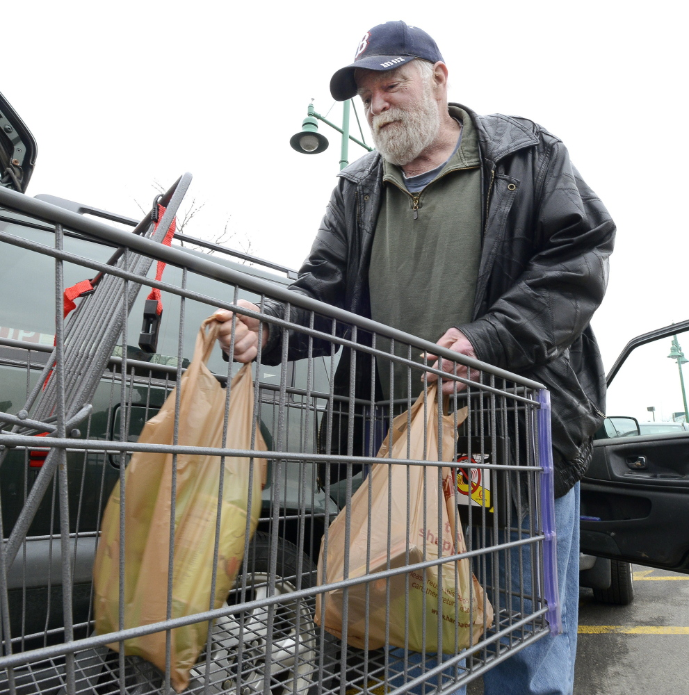 George Burnell of Portland loads plastic bags of groceries into his car at Portland's Hannaford Backbay store in April 2015 before a city ordinance went into effect to charge a nickel a bag. Members of the Sustain Mid Maine Coalition will be holding a cleanup on Tuesday, Halloween, to kick off their campaign to propose a ban on plastic bags in certain stores in Waterville.