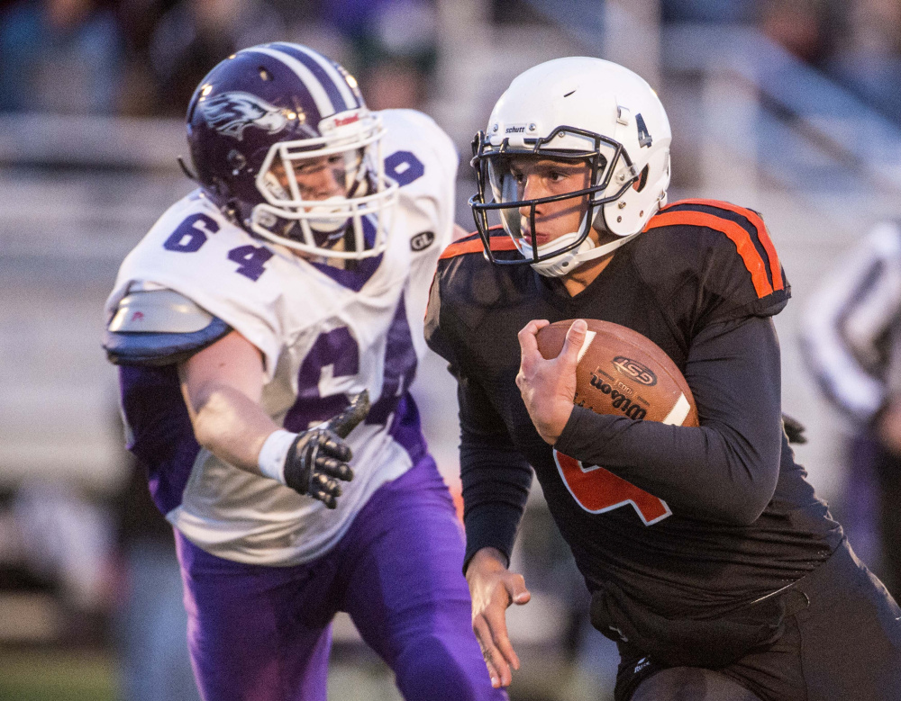 Staff photo by Michael G. Seamans Skowhegan quarterback Marcus Christopher, right, scrambles away from Marshwood junior defender Adam Doyon during a Class B game earlier this season at Clark Field in Skowhegan.