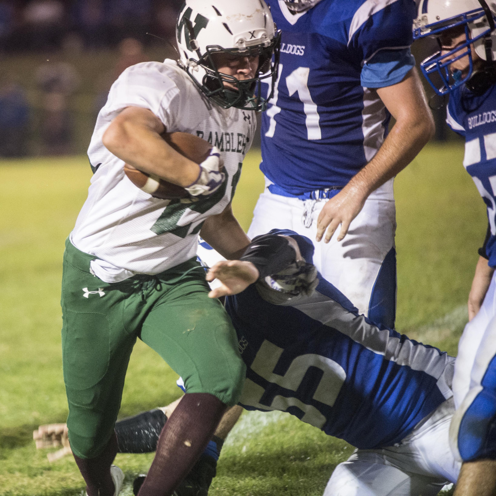 Winthrop/Monmouth running back Kane Gould runs through a tackle by Madison defender Brad Peters during a Class D South game earlier this season at Rudman Field in Madison.
