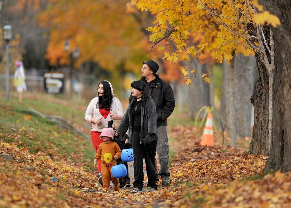 Trick-or-treaters walk down Burliegh Street looking for candy on Oct. 31, 2014.