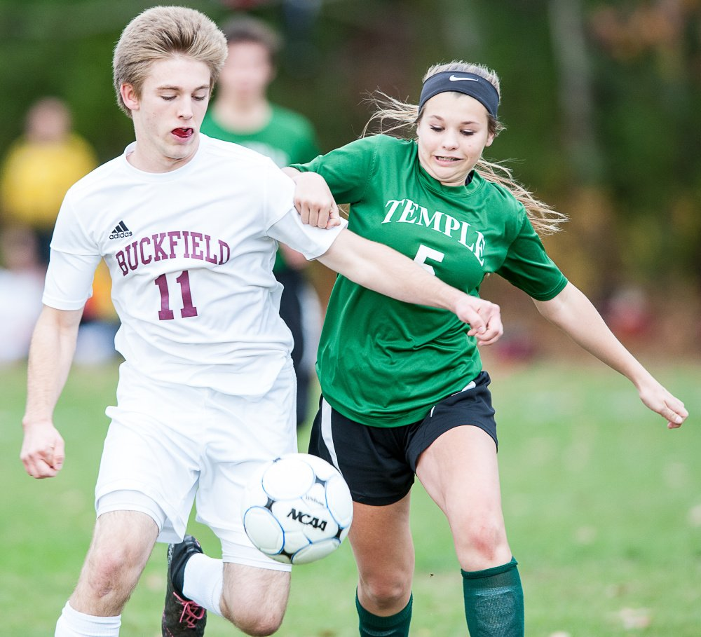 Sun Journal photo by Russ Dillingham   Buckfield's Noah Wiley (11) tries to get control of the ball as Temple's Julianna Hubbard pressures him during the first half of Tuesday's Class D South semifinal game in Buckfield.