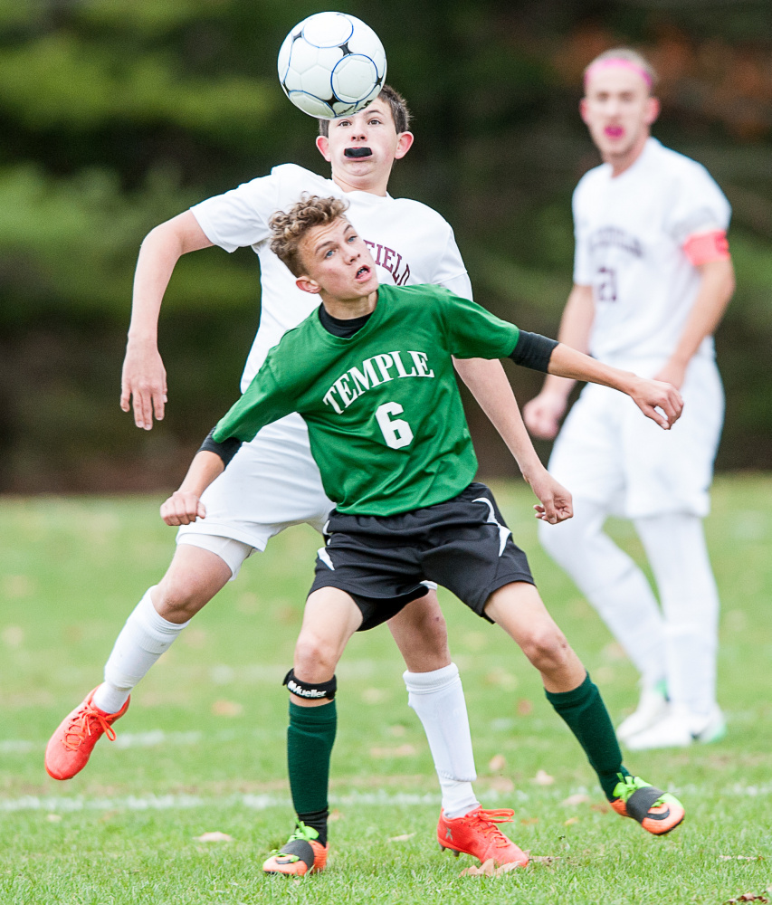 Sun Journal photo by Russ Dillingham   Temple's Nathan Riportella (6) and Buckfield's Kaleb Harvey battle for the ball during Tuesday afternoon's Class D South semifinal game in Buckfield.