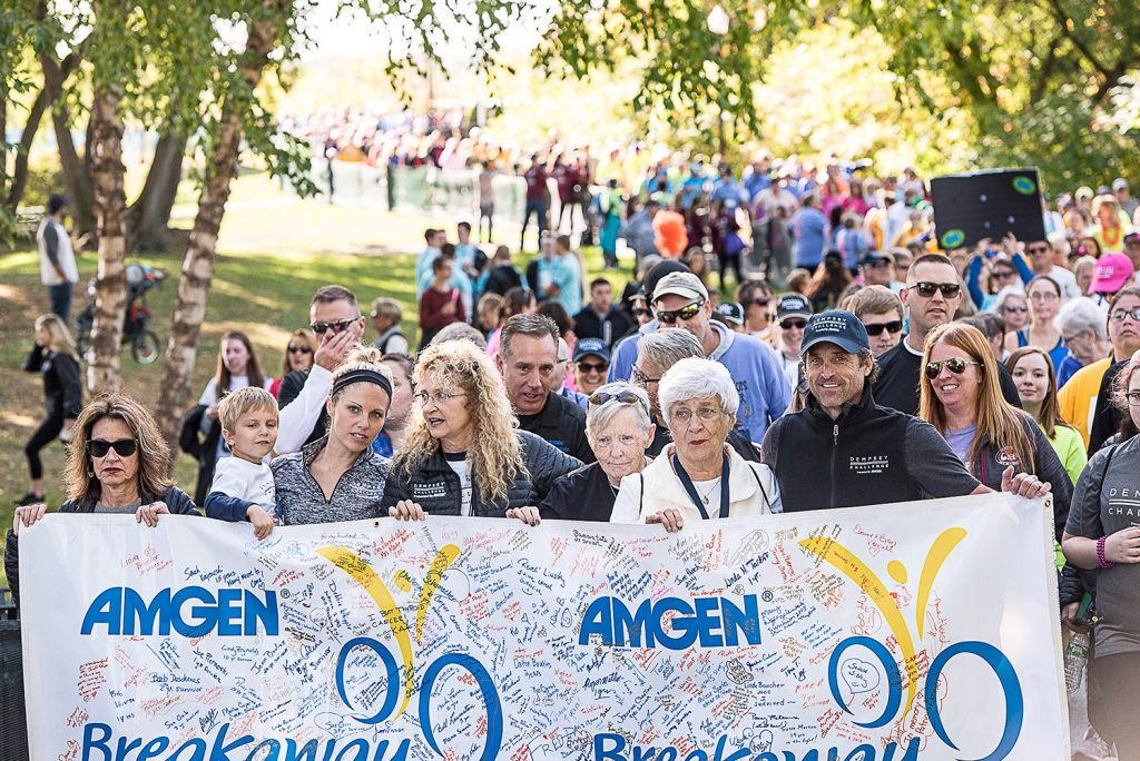 Patrick Dempsey, at the far right, holds the banner at the front of the survivors' walk through Simard Payne Park in Lewiston on Saturday as part of the Dempsey Challenge.