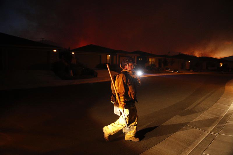 A firefighter looks for flammable items in an evacuated residential area as wildfires continue to burn on Saturday.