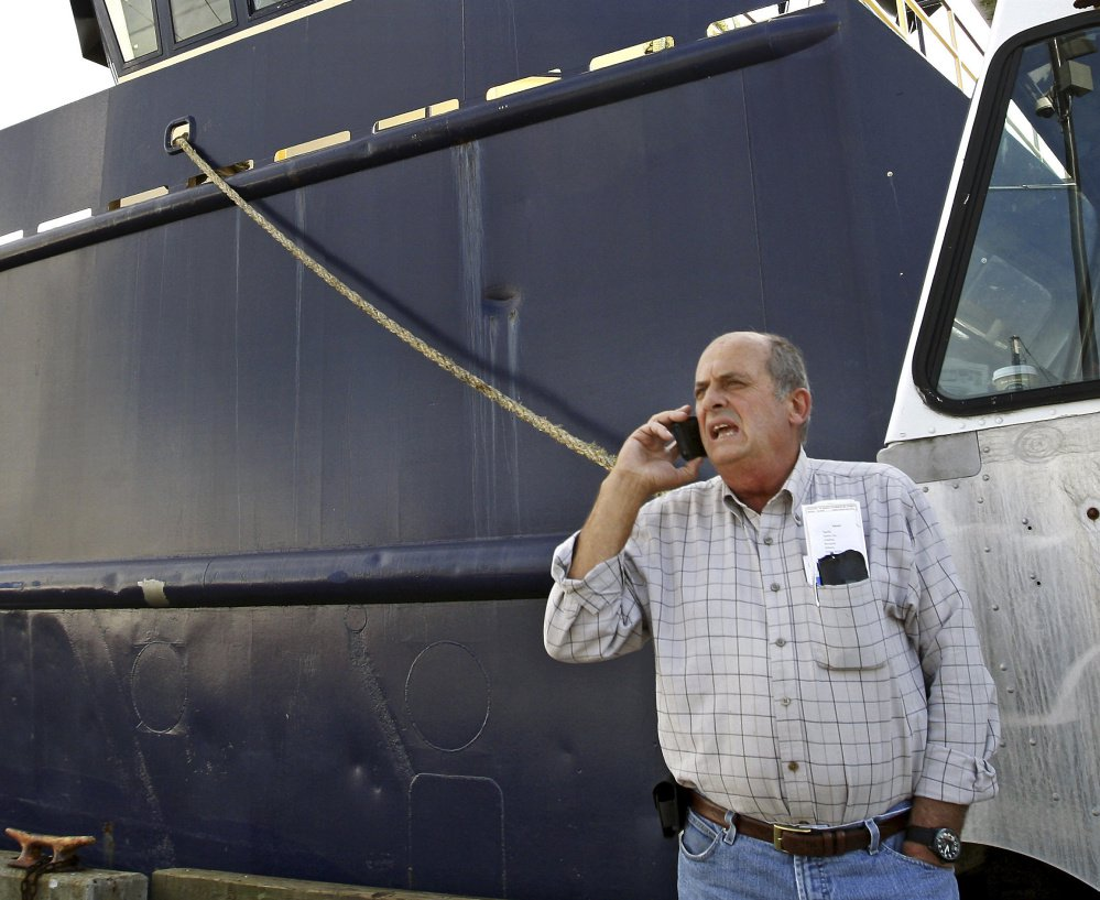 Carlos Rafael, the U.S. fishing magnate known as The Codfather, talks on the phone at Homer's Wharf near his herring boat F/V Voyager in New Bedford, Mass., in 2014.