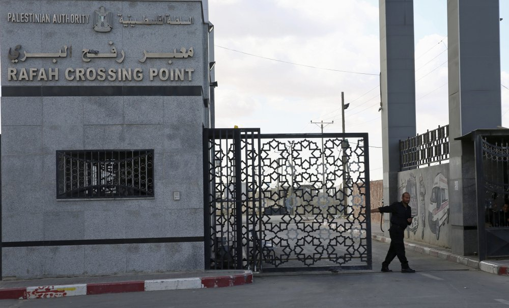 A Hamas security officer closes the main gate of the Rafah border crossing in the Gaza Strip on Tuesday.