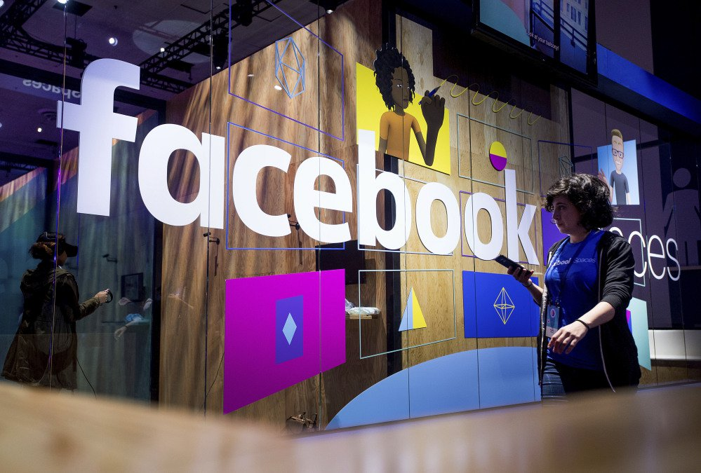 The Facebook name is displayed on a demonstration booth at the annual F8 developer conference in April. The company is doing more monitoring for harmful content.