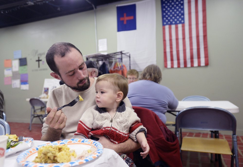 Brad Smith of Steep Falls, a village in Standish, offers his year-old son, Jensen, a bite of food during dinner Thursday at The Deeper Well Church in Standish. The church has provided the blackout-stricken community a warm refuge and hot meals every night since Monday's storm.
