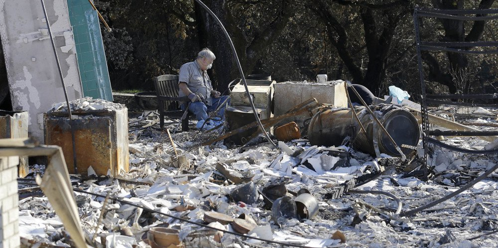 Timothy Lillyquist looks through debris at a Santa Rosa home destroyed by wildfires. Wine country got a smidgeon of rain Saturday while the mountains expected up to 2 feet of snow.