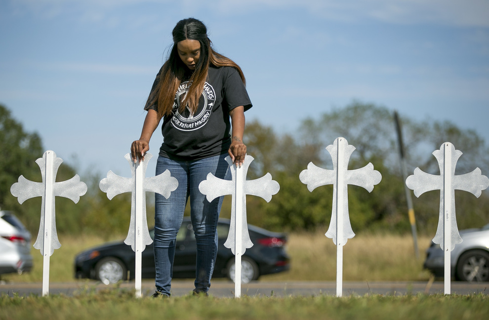 Sheree Rumph, of San Antonio, prays over two of the 26 crosses erected in memory of the 26 people killed in a shooting in Sutherland Springs, Texas, on Monday. The shooting took place during a Sunday service at the Sutherland Springs First Baptist Church.